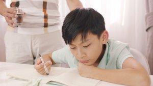 Boy pondering over homework