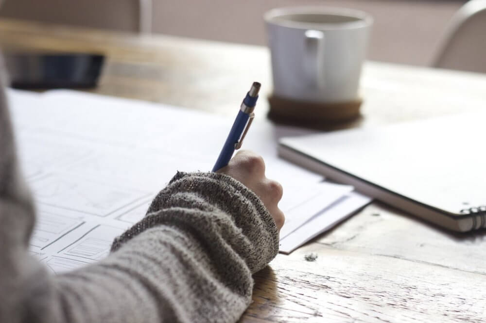 Student writing on a desk
