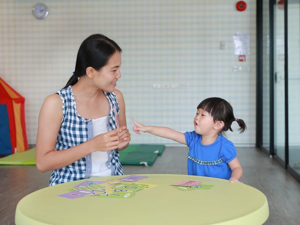 Teacher teaching child using flash cards