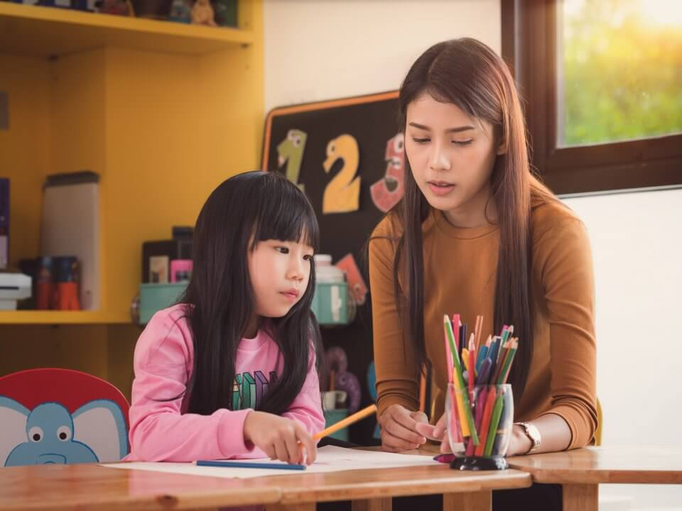 Tutor teaching a young girl