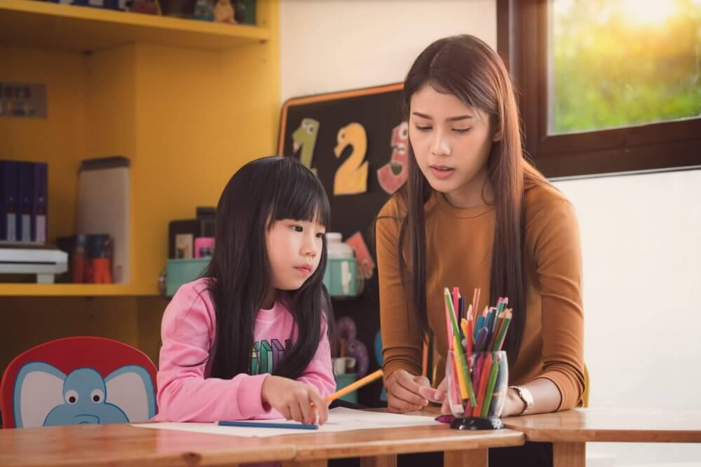 Tutor teaching a young girl