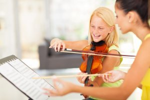 Tutor teaching violin