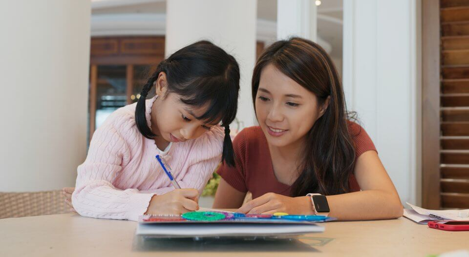 Tutor teaches girl to draw on the book